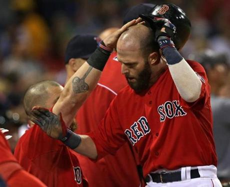 Teammates rubbed Dustin Pedroia's head after he scored in the first inning.