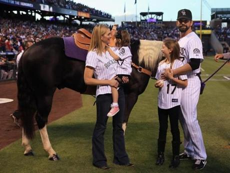 Rockies first baseman Todd Helton, his wife and his daughters eyed the horse he was given before the game as a retirement present. In his final game at Coors Field, Helton homered and had three RBIs.