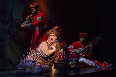 "Kevin Carolan plays Baloo in ""The Jungle Book,"" here accompanied by musicians playing trumpet, percussion, and sitar."