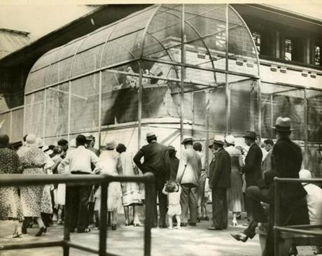 June 27, 1932:  An interested crowd looked over the bird cage at the Franklin Park Children's Zoo. There were many talking birds in the bird house, such as parrots, cockatoos, macaws and a piping crow named Impy.