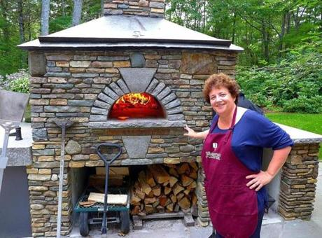 Jill Strauss of Jillyanna's Woodfired Cooking School shows off an outdoor wood-burning pizza oven.
