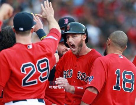 The normally stoic Stephen Drew (center) was pumped as he was welcomed back to the dugout after scoring during the Red Sox'  five-run fourth inning.
