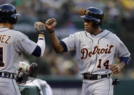 The Tigers' Austin Jackson gets a warm greeting in the dugout after scoring the game's first run in the first inning.