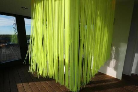 "Lynne Harlow's ""So I Built a Raft,"" an enclosed curtain of Day-Glo green ribbons that riffle on the breeze and glow beneath magenta lights."