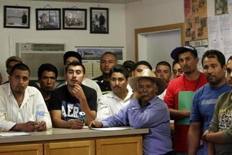 Workers who came from Mexico on a temporary H-2A agricultural work visa listened to an orientation after arriving at Stemilt Orchards in Mattawa, Wash. Even with the high percentage of noncitizens already living in Mattawa and working in the orchards there, owners say they still need to bring in more workers from Mexico.