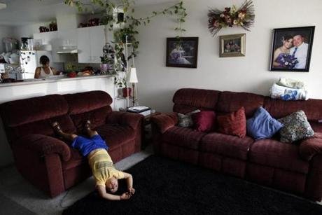 Eloy Cervantes, Jr., 6, played while his older sister, Itai, 13, cleaned the house while their parents were at work in Mattawa, Wash.