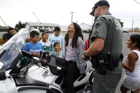 Sergeant Josh Sainsbury of the Grant County Sheriff's Department  allowed local children to sit on his police motorcycle during the Mattawa Community Days.
