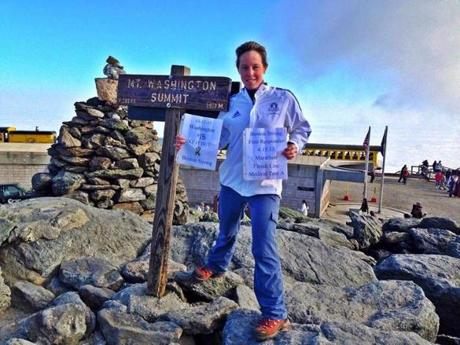 McGerald hikes to help her cope with PTSD. Here, she holds signs at the summit of Mount Washington this past weekend.