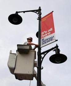 Rick Roy with Mass Bay Electric in a bucket truck worked on the new signs on the new lights.