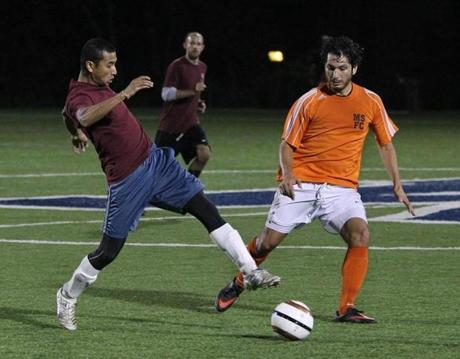 Analysis Group analyst Shailesh Munankarmi (left) went for the ball during a soccer game in Medford.