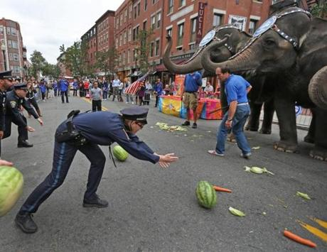 BOSTON, MA , 10 / 17 / 13: BOWLING ?????? Boston Police officers and others rolled watermellons that are a favorite desert for the elephants after they finished with their brunch. Boston Police officer Heather MacKenzie ( cq) showed off her expertise in rolling the watermellon.... Some Asian elephants from Ringling Bros. and Barnum & Bailey salute First Responders Boston Police, EMS and others in the North End by the Boston Firehouse. This was the annual North End Elephant Brunch.... ( David L Ryan/Globe Staff Photo ) SECTION: METRO TOPIC stand alone photo