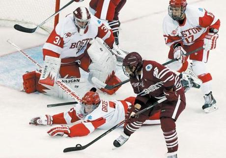 After breaking his stick, BU's Matt Grzelcyk (5) went down to block a shot by Branden Gracel (26) of UMass in first period action.