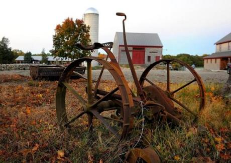 An old farm machine sits in the forground of the Hornstra's Dairy Farm in Norwell.