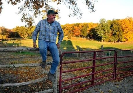 John Hornstra, talks to one of his emplyers as he sits on a fence near the barn.