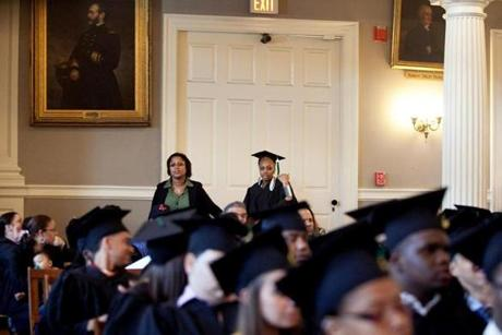 A school official escorts Natalie Davis to her seat at her graduation ceremony. The Urban Science Academy event was held in Faneuil Hall on June 6.