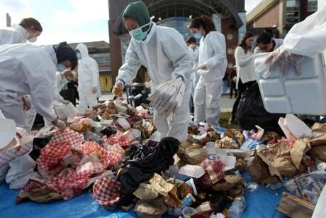 Wearing protective gear, Emily Lin (center) joined other students at Andover High School sorting through trash.