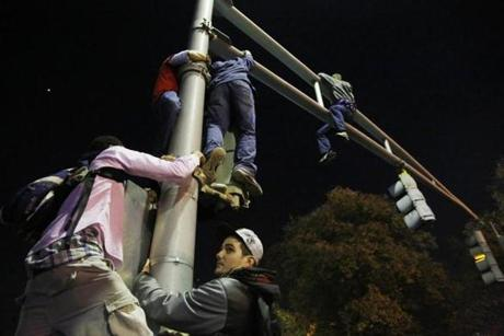 Others climbed to the top of traffic lights outside of Fenway Park.