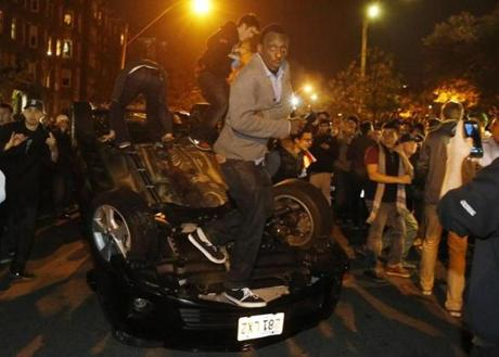 People climbed on an overturned car on Charlesgate Street.