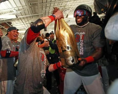 Jonny Gomes (left) helped David Ortiz open a giant bottle of champagne in the clubhouse.
