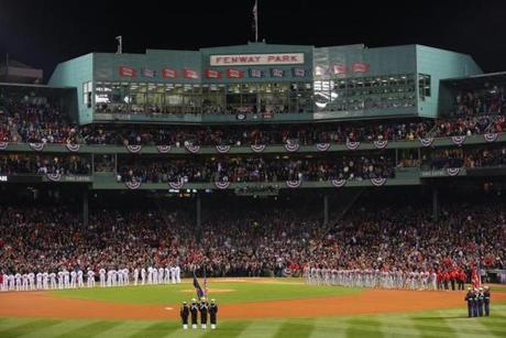The teams lined the field at Fenway Park during the ceremonies to mark the beginning of the World Series.