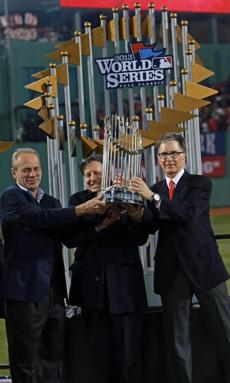 Red Sox owners Larry Lucchino, Tom Werner, and John Henry (left to right) accepted their third World Series trophy since buying the team in 2002.