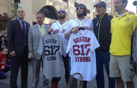 Red Sox players held jerseys as they stood in front of the World Series trophy at the Boston Marathon finish line.