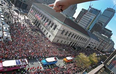 A fan on the roof of a building on Boylston Street pointed during the parade near the Boston Public Library.
