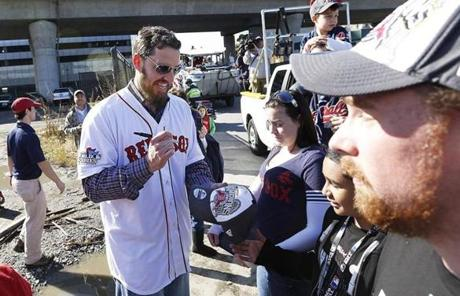 John Lackey signed a hat before the duck boats entered the Charles River.