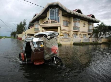 A three-wheeled motorcycle maneuvered throughn floodwaters in Taguig.