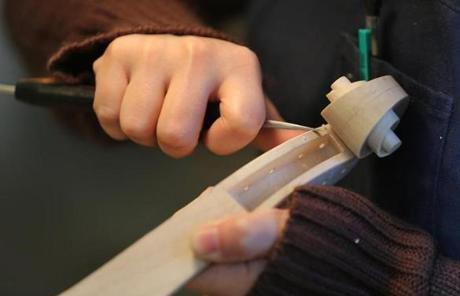 Julia Felix, a second-year student in violin making, used a violin knife to put a bevel on a scroll.