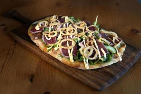 A flatbread topped with slices of tuna sashimi-style over arugula with spicy aioli.