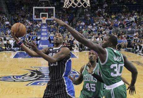 Orlando Magic's E'Twaun Moore, left, makes a shot as he gets around Boston Celtics' Gerald Wallace (45) and Brandon Bass (30) during the first half of an NBA basketball game in Orlando, Fla., Friday, Nov. 8, 2013.(AP Photo/John Raoux)