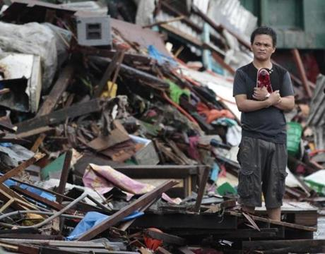 A man looked at houses damaged by the typhoon in Tacloban.