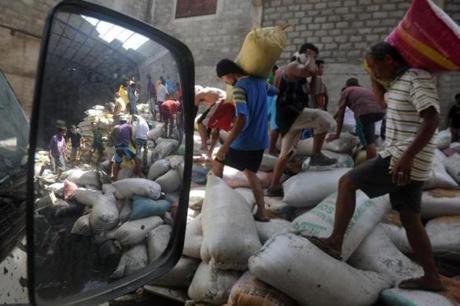 Tacloban residents carried water-damaged sacks of rice from a warehouse in the aftermath of the typhoon.