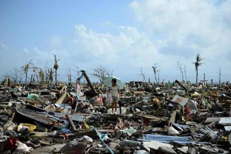 A surivor walked among the debris of houses destroyed by Typhoon Haiyan in Tacloban.