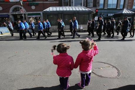 Two-year-old twins Francesca and Isabella Cohoon of Marshfield waved their flags as Boston's Veterans Day parade made its way down Tremont Street and around the Boston Common.