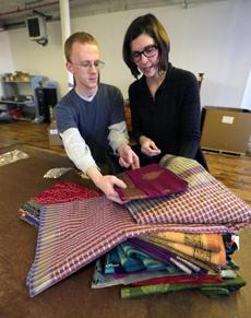 Lawrence, MA - 11/14/13 - Brenna Schneider, cq, Founder and CEO of 99degrees Custom who has a MBA in Social Impact Management from Brandeis University, looks over fabric for Lallitara with fabric cutter Mark Currie, cq, at the Custom Apparel Manufacturing Company headquarters in Lawrence. - (Barry Chin/Globe Staff), Section: Business, Reporter: Robert Gavin, Topic: 16brandeis, LOID: 6.2.2609566970.