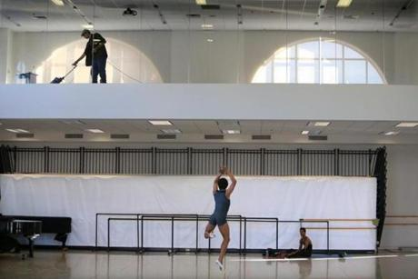 Jim Mullarkey, facilities coordinator at the Boston Ballet practice site on Clarendon Street, vacuumed an upstairs room while company dancer Irlan Silva rehearsed below.