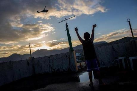 A young boy waved to a helicopter from his home's rooftop in Leyte.