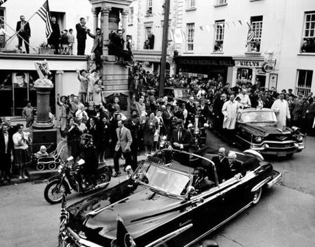Cheering people crammed the streets and even perched on the narrow cornice of a building as they welcomed US President John F. Kennedy on his visit at their hometown New Ross, Ireland, June 27, 1963. The motorcade was en route to the quay where the President's great-grandfather allegedly boarded a ship bound for the United States 120 years prior.