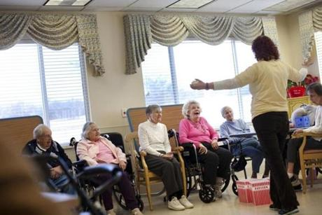 Activities assistant Irene Hudson led residents, from left, Charles Kennelly, Ann Mazurek,  Hermine Hatalski, Rosemond Curley (hot pink), and Marjorie Bontempo (light blue) in a ball-tossing game at Life Care Center of Nashoba Valley. The center reduced the use of antipsychotics by focusing on other ways to calm and comfort patients.