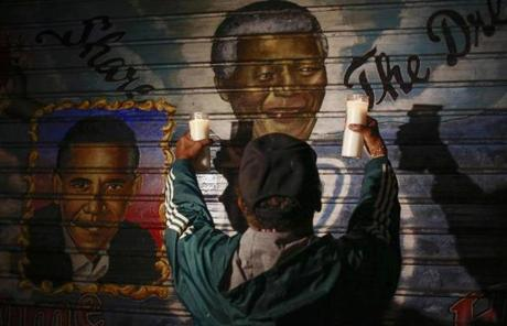 A man held candles in front of a mural of Mandela and Obama in New York.
