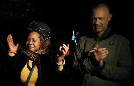 Two people sang at a gathering in memory of Mandela outside the South African High Commission in London.