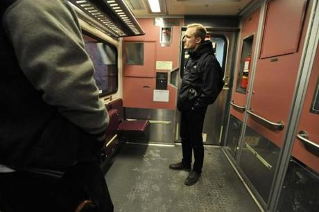 Casey Nealon of Boston waits by the door as the train approaches his stop in Salem.
