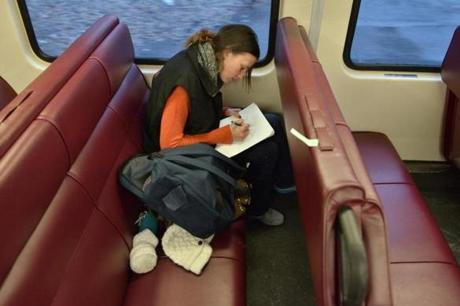 Amanda Tower of Rockport, a Salem State student, works on her classwork on the train.