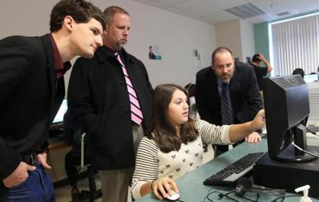 "Littleton seventh-grader Christina Tsillas shares her ""Hour of Code'' project with (from left) school board member Alex Pratt and school principals Scott Bazydlo and Mark Branco."