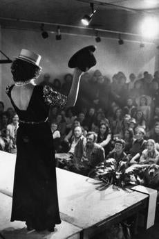 March 22, 1975: Fellini's Basement was the catchy theme of the Boston Visual Artists Union Gallery when the gallery space was turned into a replica of Filene's Basement. More than 900 artists and friends of the Union contributed finery to the auction affair which raised money for the gallery. Here some hats were auctioned off.