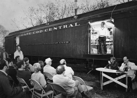 May 14 1973: Auctioneer Robert D. Thompson of Centerville asked for auction bids from the door of a baggage car which served as headquarters for the Cape Cod Model Railroad Club. Nearly 100 model trains, tracks, books and other railroad paraphernalia were auctioned off to raise money for the club. Every Friday night members gathered at the restored passenger car to work on rebuilding in miniature the famous railroad lines that once serviced Eastern Massachusetts.