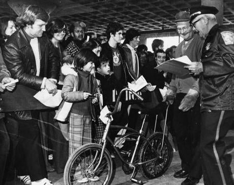 December 6, 1975: The crowd viewed a bike before the bidding started at the Boston Police Department's auction of unclaimed stolen and lost property in Dorchester. The bike sold for $16.