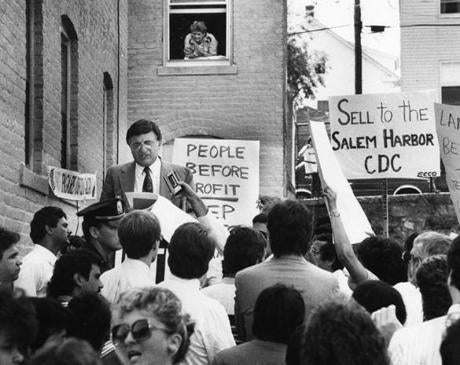 August 2, 1989:  Auctioneer Paul Saperstein auctioned off a building on Peabody Street in Salem as the crowd protested. More than 200 apartment tenants who feared rent increases disrupted the foreclosure auction by clapping and chanting. Six of the eight properties up for auction were blocked from being auctioned off by the protestors.